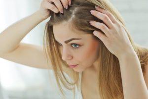 Žena si kontroluje pokožku na hlave