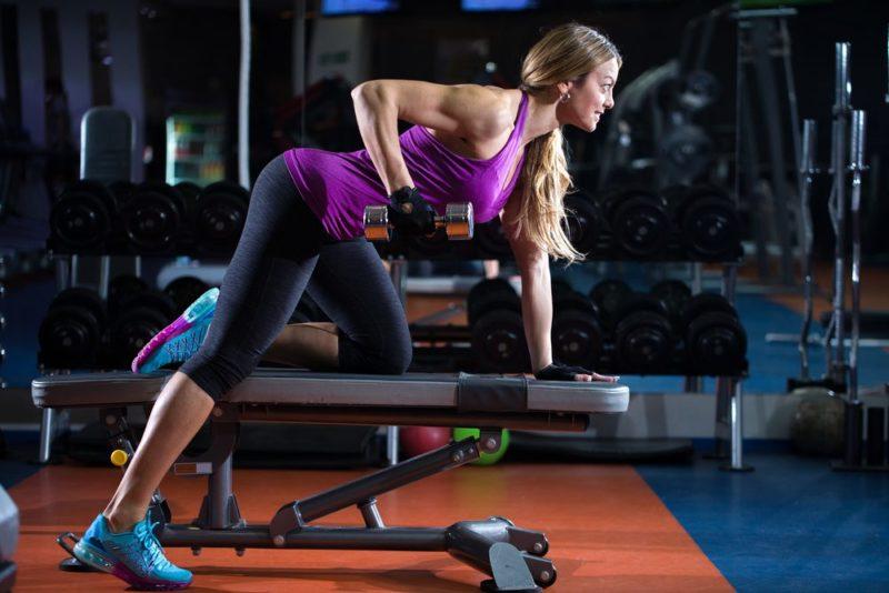 žena cvičí triceps na lavičke s jednoručkou