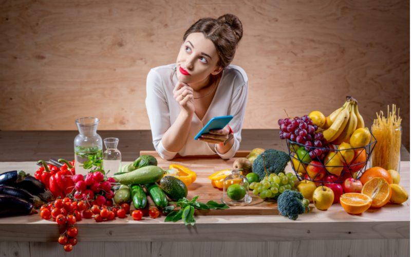 žena počíta kalórie ovocia a zeleniny s pomocou kalorických tabuliek