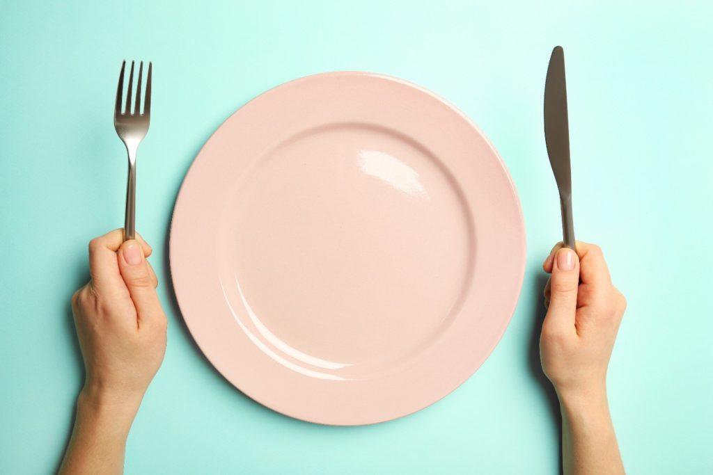Breussova diéta a chudnutie - prázdny tanier a príbor v ruke