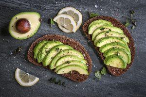 prepolené avokádo a celozrnný chlieb s plátkami avokáda