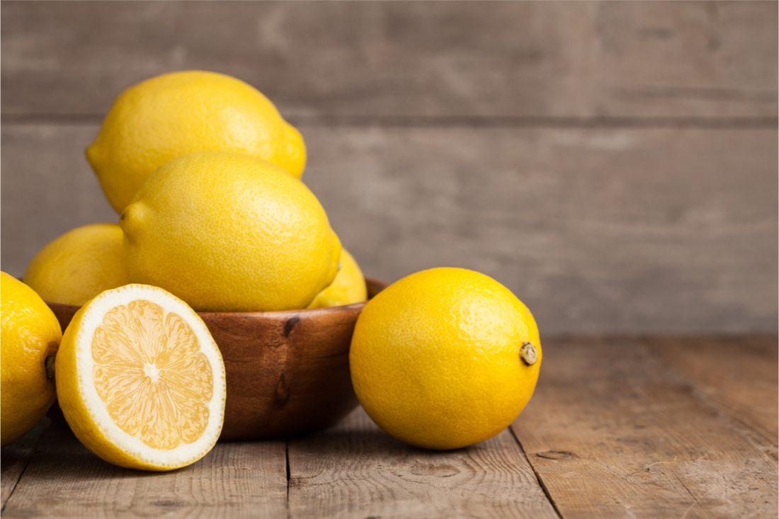 citróny v miske a prekrojený citrón na drevenom pozadí