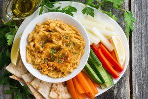 mrkvový hummus v miske na tanieri s čerstvou zeleninou a arabským chlebom