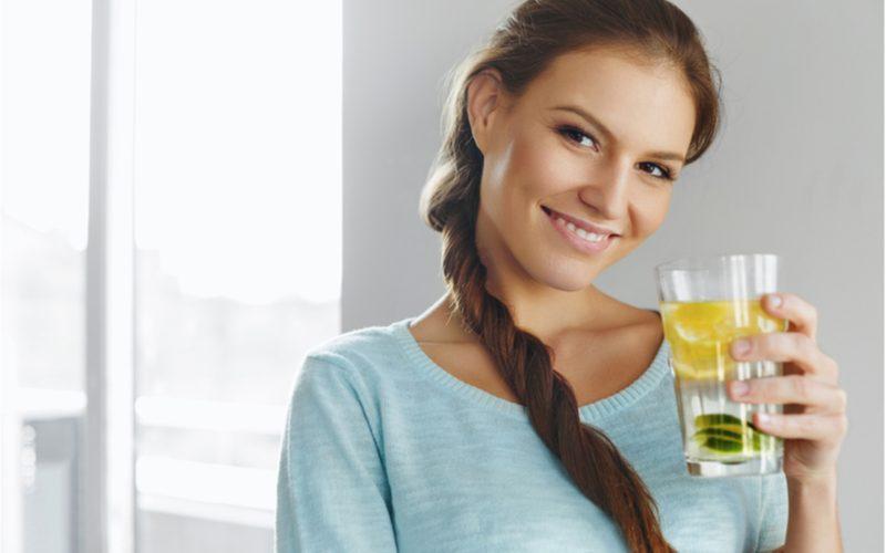 žena držiaca pohár s vodou a citrónom