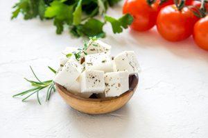 kocky ovčieho syra v malej miske na bielom pozadi