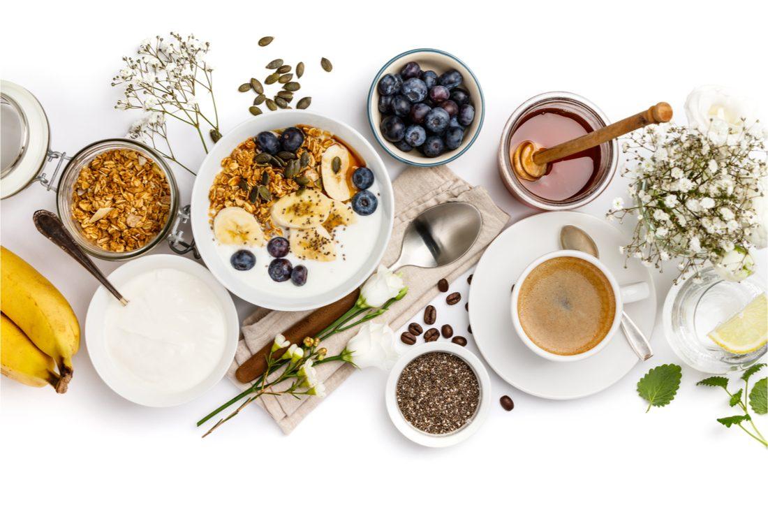 misky s ingredienciami, ovocím, vločkami a medom na bielom podklade
