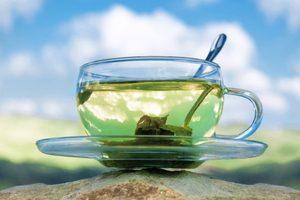 šálka so zeleným čajom na pozadí modrej oblohy