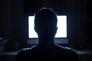 silueta hlavy muža pred obrazovkou počítača