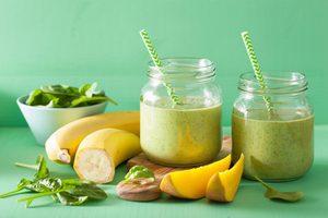smoothie v pohároch, miska s listovým špenátom a prekrojený banán