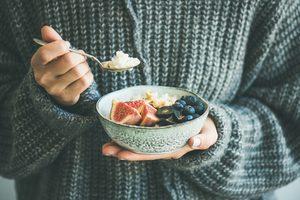 žena v svetri držiaca misku, v ktorej sú zdravé raňajky