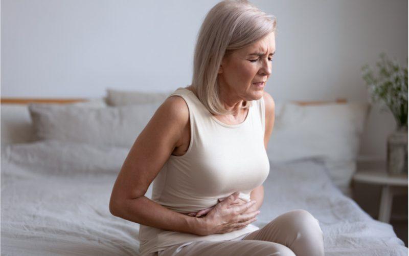 žena sediaca na posteli držiaca sa za brucho - bolesti pankreasu