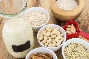 karafa s rastlinným mliekom a misky s orechmi a obilninami