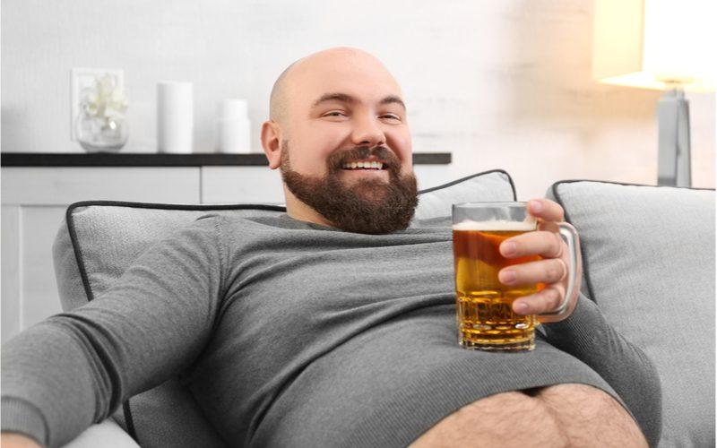 muž na pohovke s pohárom piva položenom na svojom vypuklom bruchu