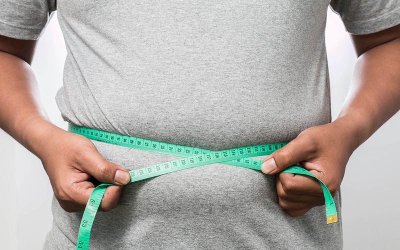 muž s nadváhou na bielom pozadí, merajúci svoj obvod pásu