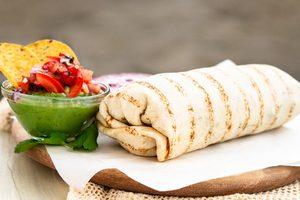 tortila wrap na obrúsku, vedľa miska s avokádovým guacamole
