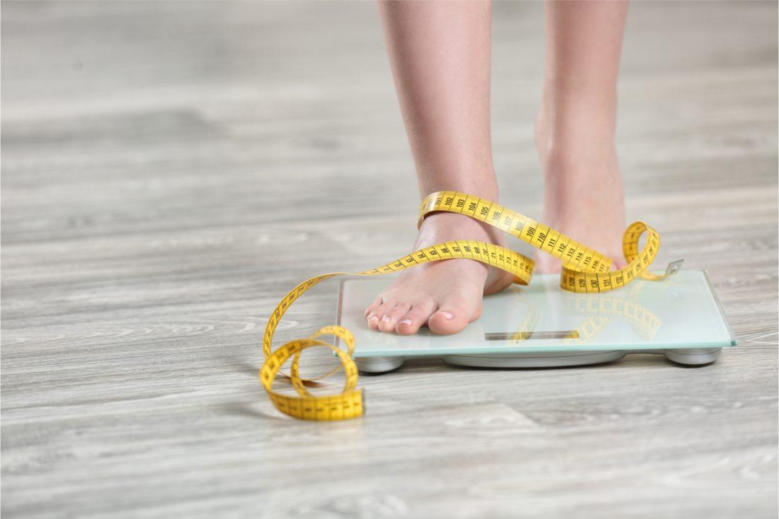 ženské nohy omotané žltým centimetrom stúpajúce na váhu