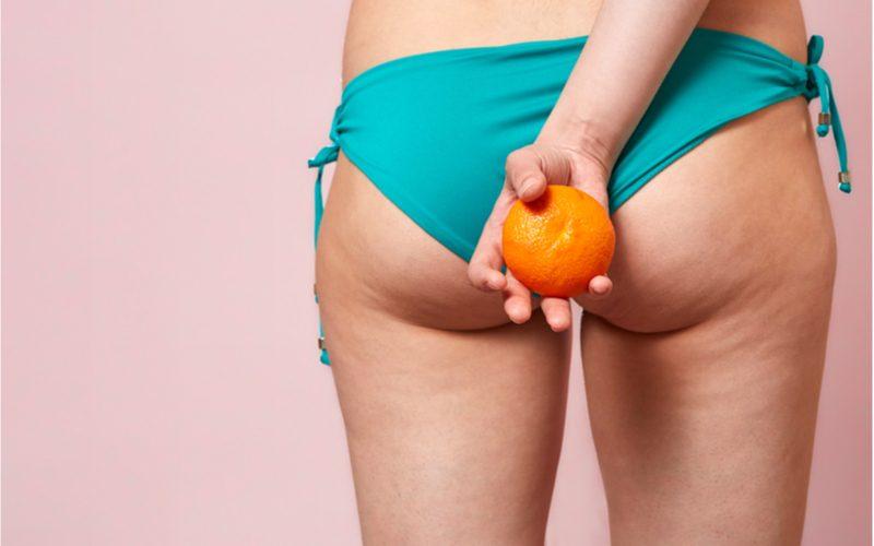 záber na ženský zadok a stehná s celulitídou, pomaranč v ruke