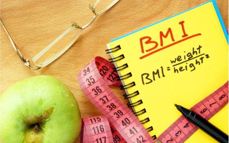 žltý zošiť s výpočtom BMI, centimeter, jablko a okuliare na stole
