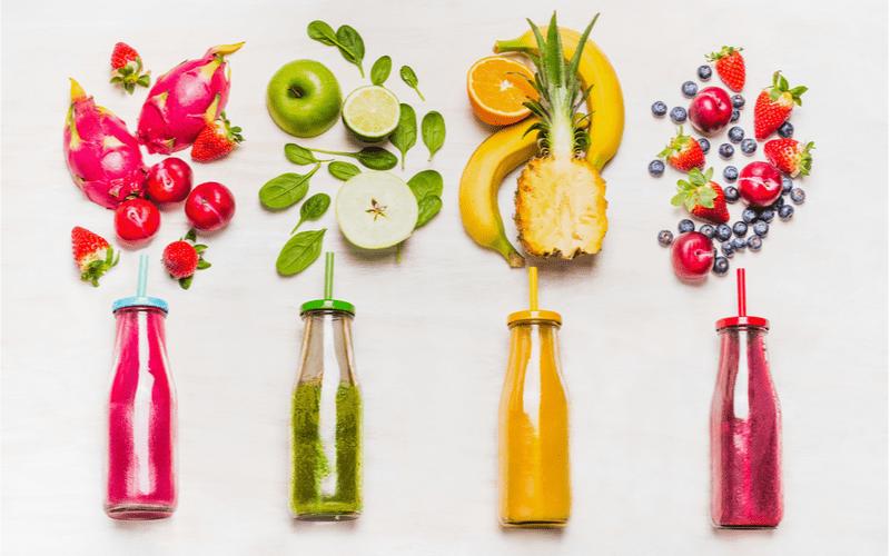 4 fľašky so smoothies a rôzne druhy ovocia na bielom pozadí