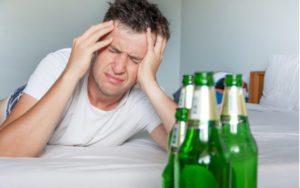 Muž s bolesťou hlavy po konzumácii alkoholu