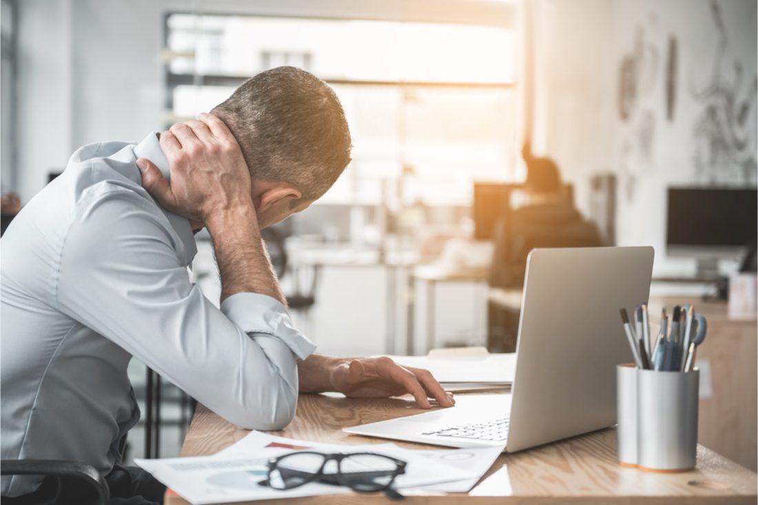 muž sediaci v kancelárii sa drží za boľavý krk