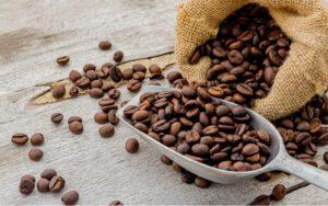 Kávové zrná v naberačke a vo vrecku