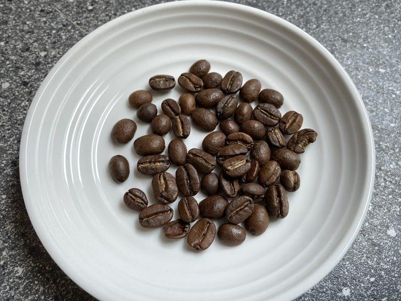 Kávové zrná na bielom tanieri
