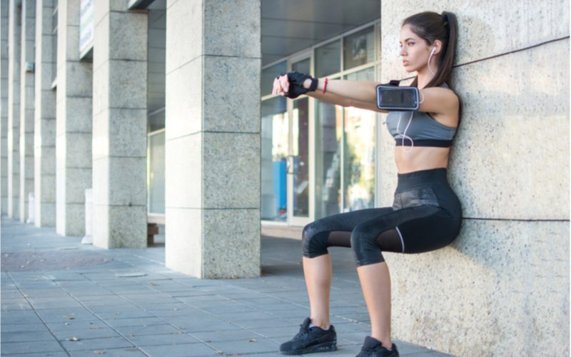 mladá žena cvičiaca vonku v meste wall sit