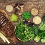 tmavý celozrnný chlieb a zelená zelenina na drevenom povrchu