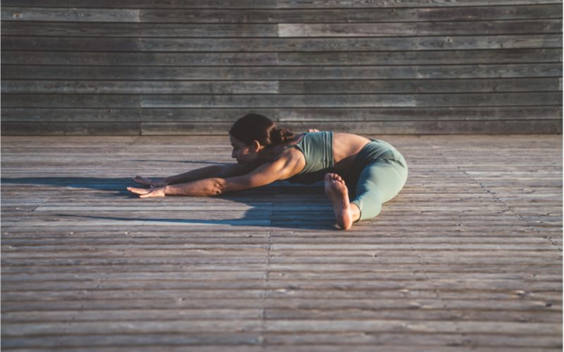 mladá žena v hlbokom predklone - cviky na nohy