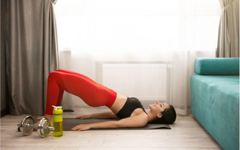 žena v červených legínach cvičiaca zdvíhanie panvy