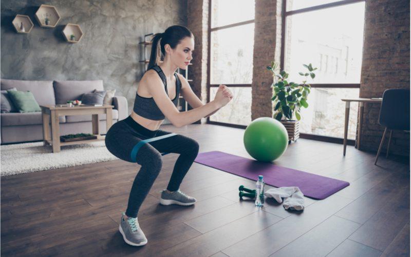 mladá žena cvičiaca drepy s pomocou odporovej gumy