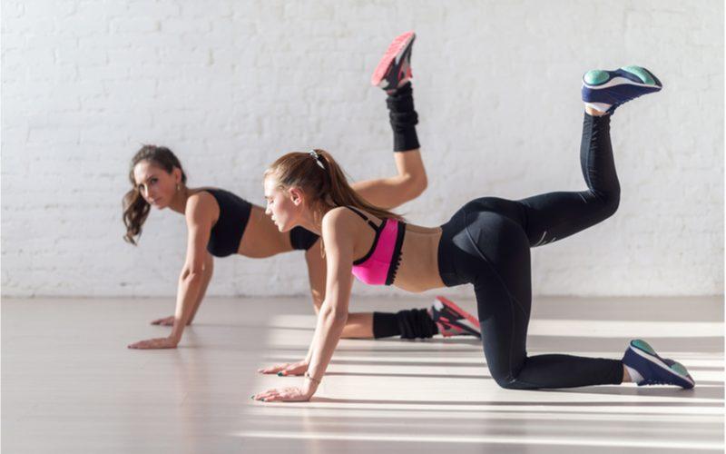 dve ženy cvičiace zakopávanie nohou na štyroch