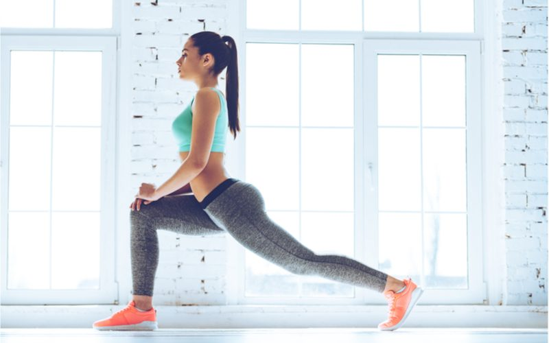 mladá vyšportovaná žena precvičujúca nohy